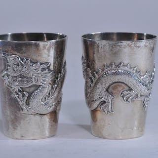 Pair of small silver cups. Dragon decoration on each.