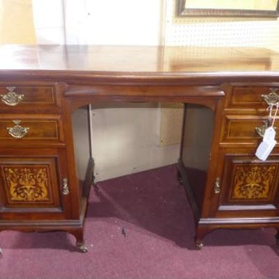 An Edwardian marquetry inlaid mahogany knee hole desk, raised on castors