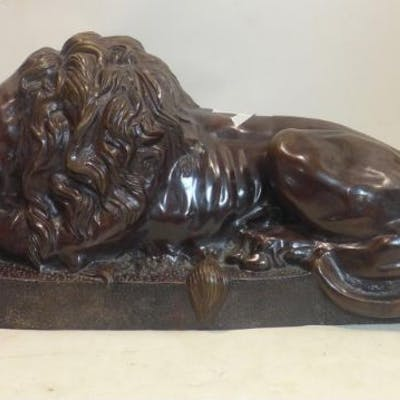 A 20th century large cast bronze study of a recumbent lion, H.51 W.114 D.45cm
