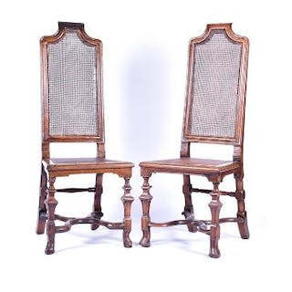 A pair of 17th century style walnut hall chairs with cane seats and