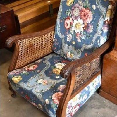 A carved mahogany bergere armchair with blue floral upholstery