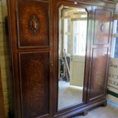 A c1920's Jacobean Revival oak triple wardrobe with a central mirrored