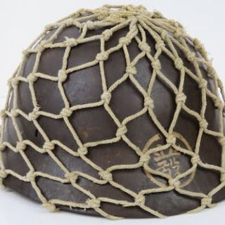 A WWII Japanese Military Infantry issue helmet with scrim netting