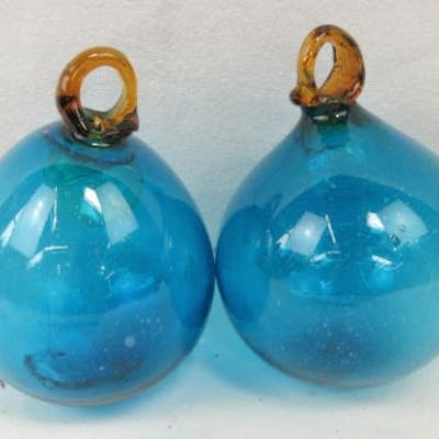 Two decorative blown blue and amber glass baubles.