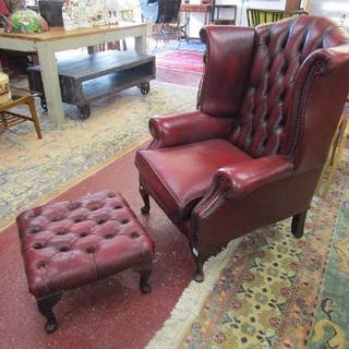 Red leather buttoned wing-back armchair with matching footstool