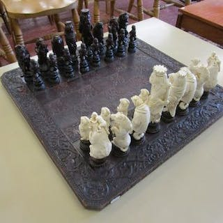 Chess set with ornate carved chess board
