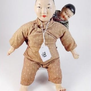 An early 20th century Japanese papier mache doll with baby doll 25cm tall