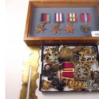 A group of WW2 medals in mahogany case with a collection of military cap badges