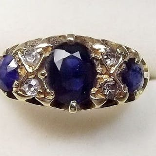 An 18 carat gold ring set three sapphires and two pairs of diamonds size O