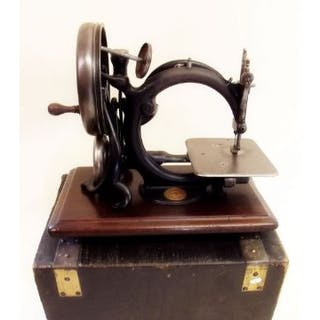 A 19th century Wilcox and Gibbs sewing machine with case