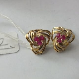 Pair of 9ct. knot clip earrings, each with three ruby coloured stones 4g.