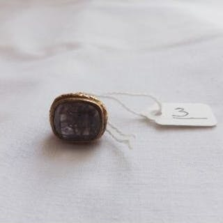 An antique 9ct gold seal with amethyst coloured intaglio