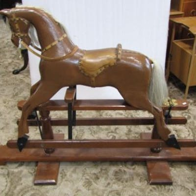 A traditional wooden rocking horse with brown painted colourway, raised
