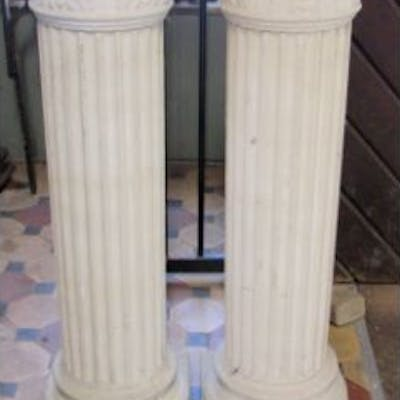 A pair of buff coloured pedestals with classical cylindrical fluted