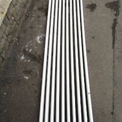 A white painted cast metal radiator with tubular bars, 2m long x 50cm high