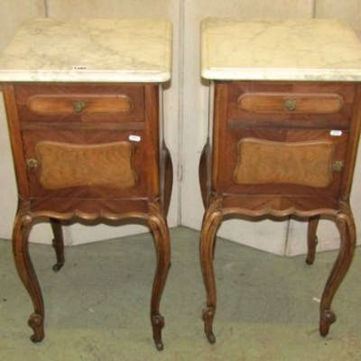 A pair of walnut veneered pot cupboards, each enclosed by a panelled