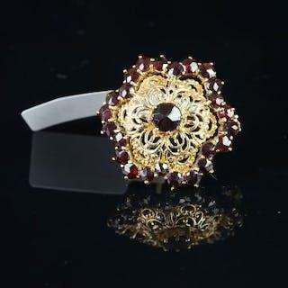 A garnet floral brooch, with a central rose cut garnet, openwork design