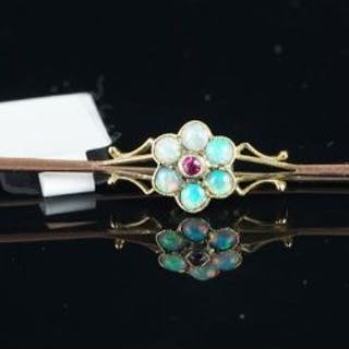 An opal and ruby bar brooch, central round cut ruby surrounded by