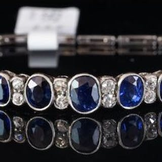Sapphire and diamond bangle, seven graduated oval cut sapphires, measuring