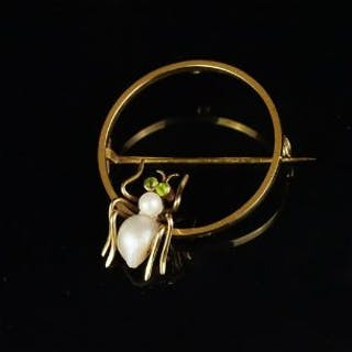 Spider brooch, pearl body, with peridot set eyes, on a yellow metal