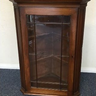 An oak corner cupboard with bevelled glass. Est. £