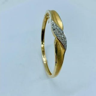 A 14ct yellow gold and diamond hinged bangle