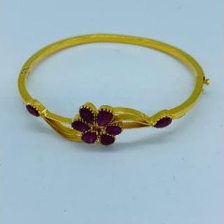 A 22ct gold and ruby bracelet with a floral motif.