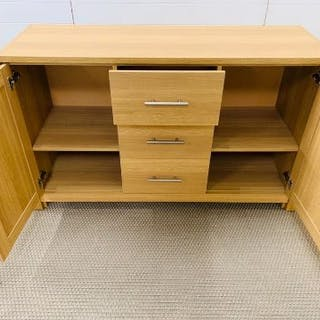 A sideboard unit with door to each end and three central drawers