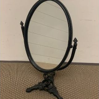 An oval table mirror on wrought iron frame