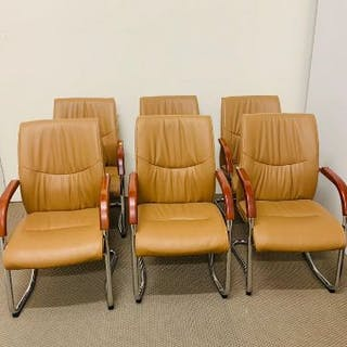 A six leather boardroom chairs with wooden arm rests on chrome frames