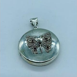 A silver photo locket with embossed butterfly set with ruby and emerald