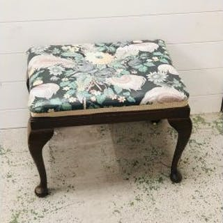 A small upholstered footstool on cabriole legs