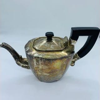 A Sterling Silver Teapot with ebony style handle and ornate spout.