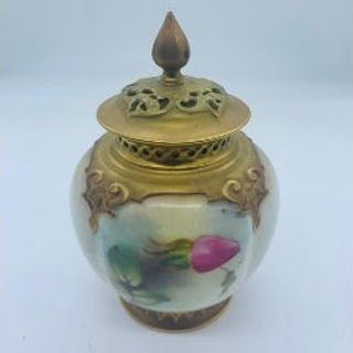 A Royal Worcester lidded vase with repairs to finial and lid.