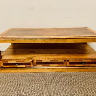 A solid coffee table with storage drawers and lower shelf