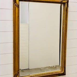 A large ornate gilt framed bevelled mirror (105cm x 75cm)