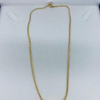 An 18ct yellow gold necklace (Marked 750) with central emerald with