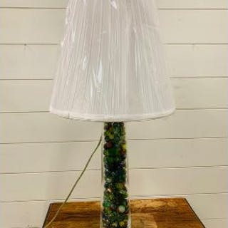A glass table lamp filled with marbles