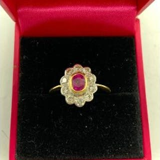 An 18ct yellow gold ruby and diamond flower head style ring