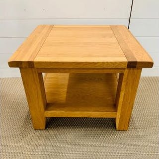 An oak square occasional table with shelf under