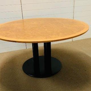 A large round walnut veneer table