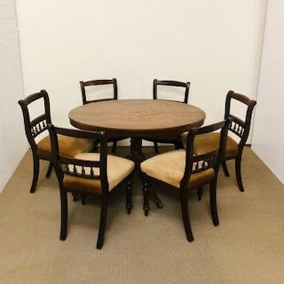 An oval breakfast table with marquetry detailing on tripod base with six chairs