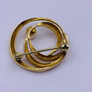A gold brooch with a single pearl