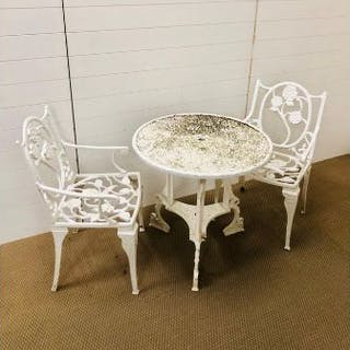 A white painted cast iron garden table with two chairs with arm rests
