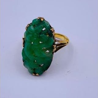 A Chinese jade ring on gold band with indistinct hallmarks