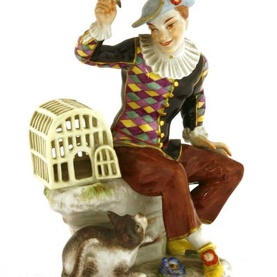 A Meissen figure of a seated harlequin