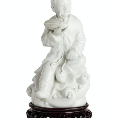 A BLANC-DE-CHINE PORCELAINE FIGURE OF A SEATED BOY, CHINA, 20TH CENTURY; WEAR