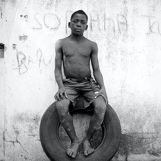 Sitting on a tire - Mário Macilau