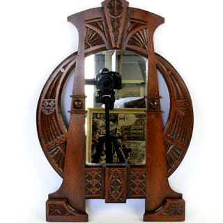 An Art Nouveau mahogany wall mirror in the style of Carlo Bugatti