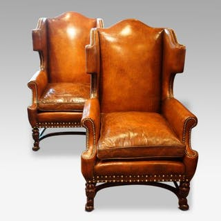 Pair of carved oak and leather wing chairs